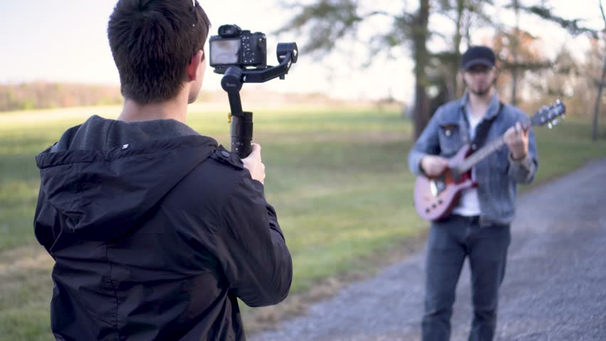 Using a gimbal, a teen filmmaker walks backwards filming a music video with a guitar player singing and walking while playing.