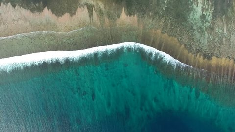 Aerial top view of blue waves of ocean running to black coastline foaming during tide bringing seaweed, bird's eye view of seascape with turquoise water near shore shallow lands with dark sand