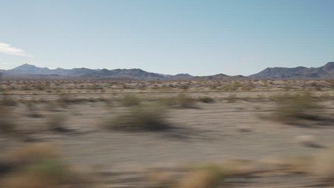 Driving plate side view moving through desert in car