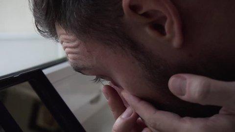 Closeup of man insterting contact lens