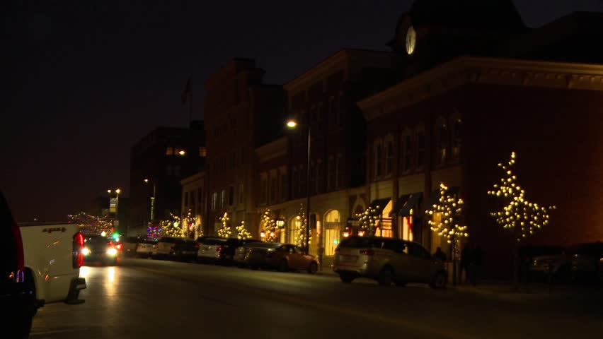 Christmas lights decorate the city streets in a small town in the Midwest. The clock in the tower is lit up as cars drive along the business district and people shop for gifts for the holiday season.