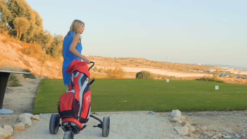 Happy woman with golf trolley comes to golf course