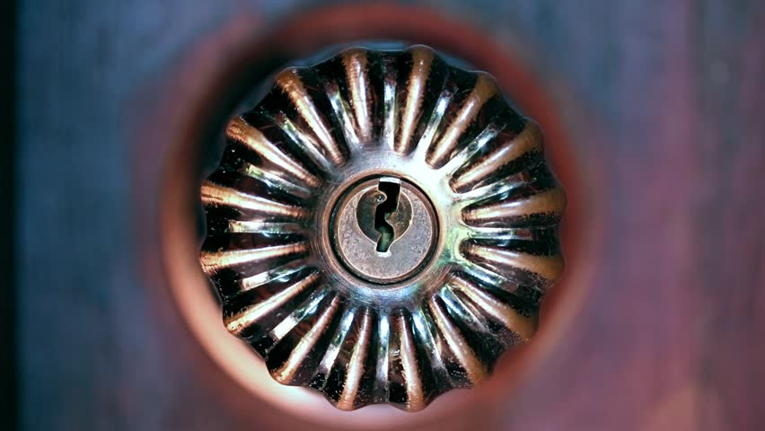 The hand holds the door-knob and open the door. Open the house. Close up old decorative door-knob on wood door. Detail of a aged round ball door knob on brown door.