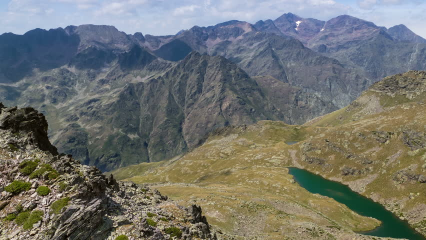 """Landscape of mountains, with  the """"Caraussans"""" lake, and the sky with  fast movement of clouds, shadows and sunlight in """"ORDINO, ARCALIS"""",  Pyrenees of Andorra.Time lapse."""