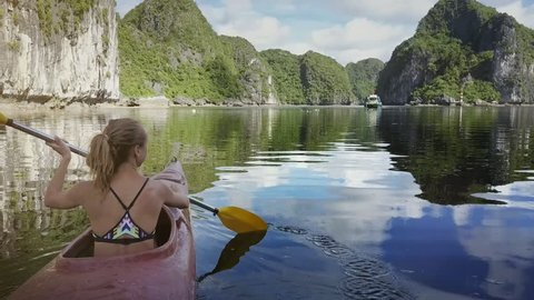 backside closeup blond girl oars kayak in ocean bay with pictorial green and rocky islands reflected in tranquil water