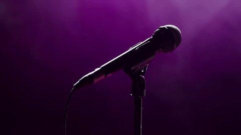 Microphone in hand singer on stage. Close-up. Silhouette of singer on stage with microphone in hand. Dark background, smoke, spotlights.
