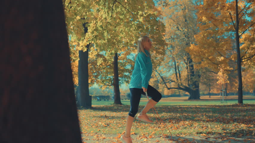 Fitness woman jumping rope. Female is jogging in sunny day light in the autumn trees background, girl training outdoors on fall day, 4K | Shutterstock HD Video #33790312