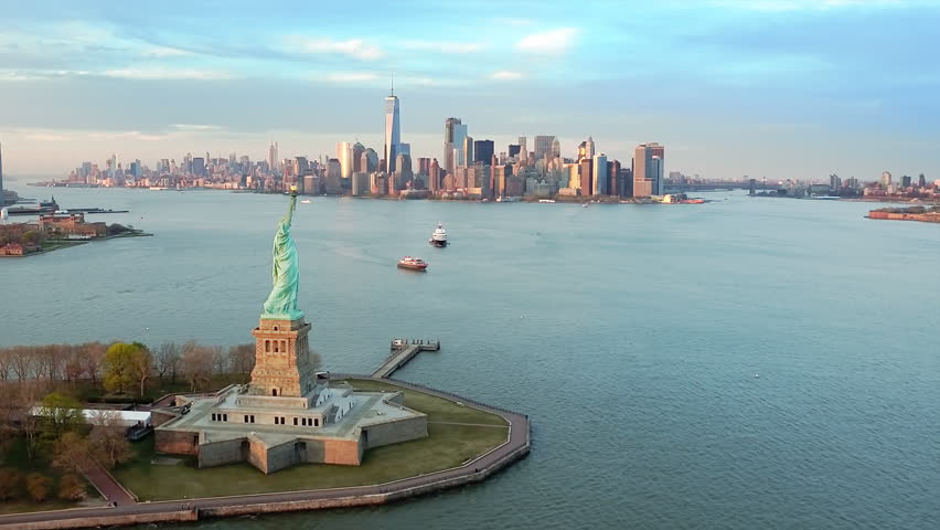 Aerial view of the Statue of Liberty at sunset. Manhattan and New Jersey skyline in the background. New York City, United States. Shot from a helicopter. #33800842
