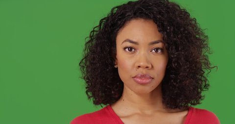 Close up portrait of pretty black woman looking directly at camera on greenscreen background. Close-up of serious African American millennial on green screen for keying or compositing. 4k