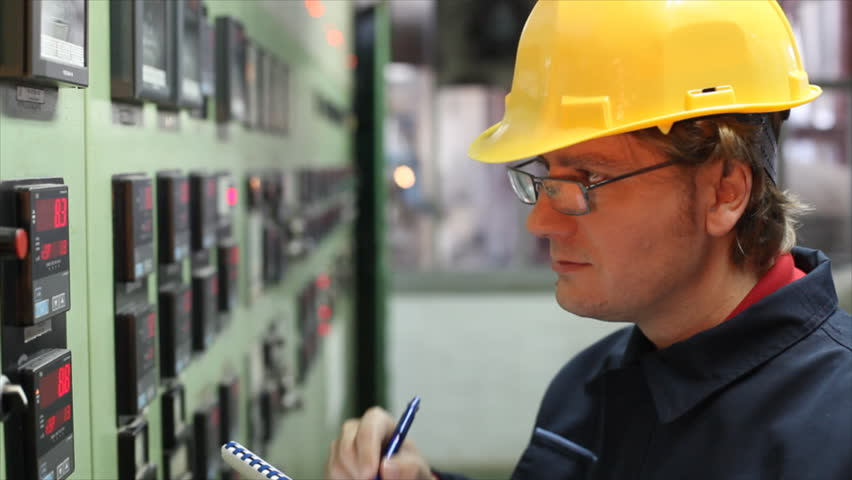 The worker writes the results of measuring devices in the control room at the factory. Shallow Doff, selective focus.