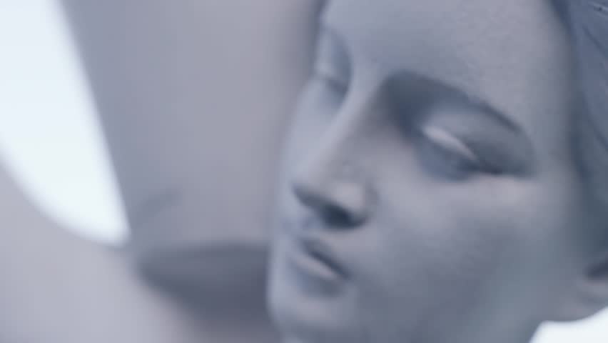 Close up slow motion shot of a woman's statue. Classic sculpture in the park