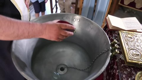 pouring oil in water during christening or baptism