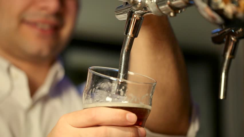 Barman filling a glass of beer in a pub