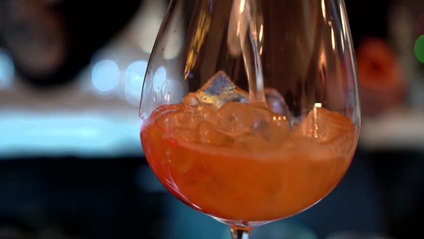 A bartender silhouette fills a transparent glass goblet with reflections with ice cubes and orange-colored alcohol drink on a bar background, close-up. Slow motion with blur bokeh lights.