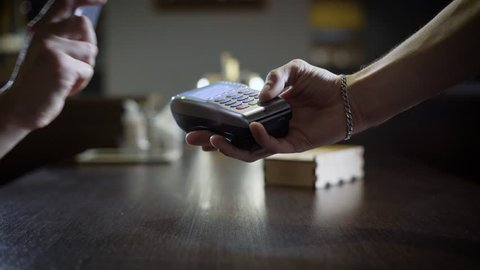 people are using contactless payment by phone in a restaurant, hand with smartphone is touching payment terminal