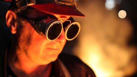 Hard work in the foundry, worker watching and controlling iron smelting in furnaces, too hot and he putting protective eyewear