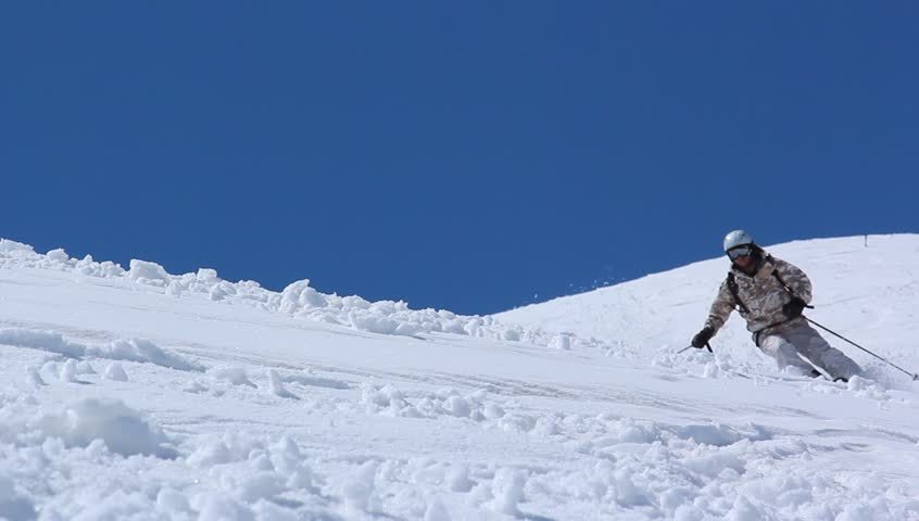 Skier close-up in soft snow on a sunny give against the clear sky | Shutterstock HD Video #3386243