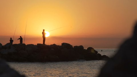 Silhouette of a fisherman, man fishing on a sea from the rock at sunset. 120fps