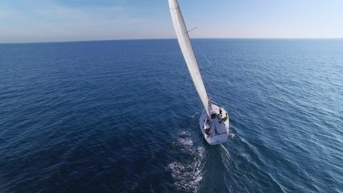 Beautiful epic drone aerial footage on warm sunny day at blue open ocean at sea, white professional yacht during racing competition, full open sails, spinnaker and mainsail at mast