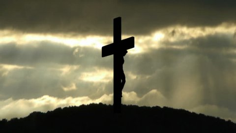 Silhouette of the Holy Cross on background of storm clouds.