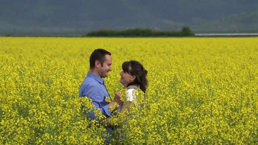 Romantic couple in blossom rape field, man arrange a flower in woman hair