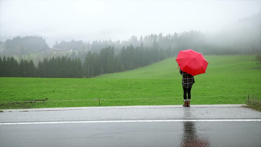 Lonely woman under umbrella in rainy day