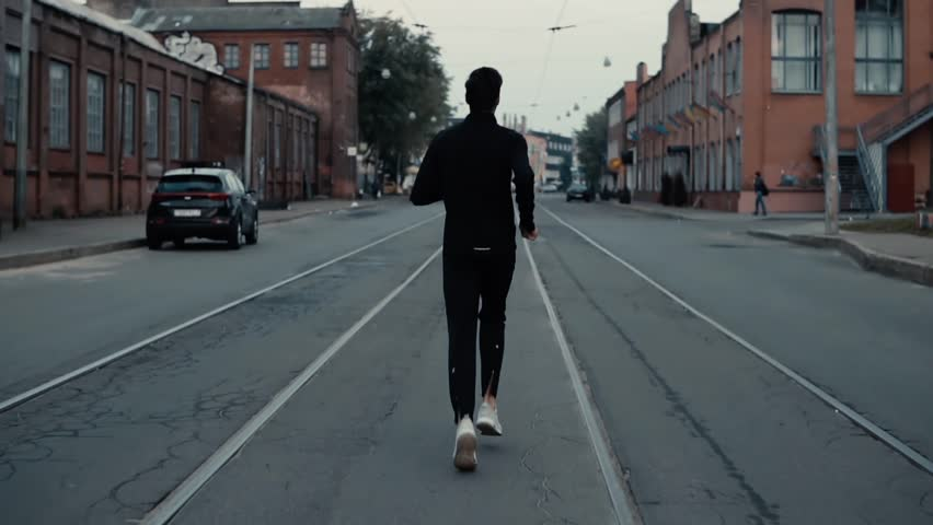 Sportsman running between tram tracks. Background shot. Slow motion. Concept of strong individuality and confidence. #33920152