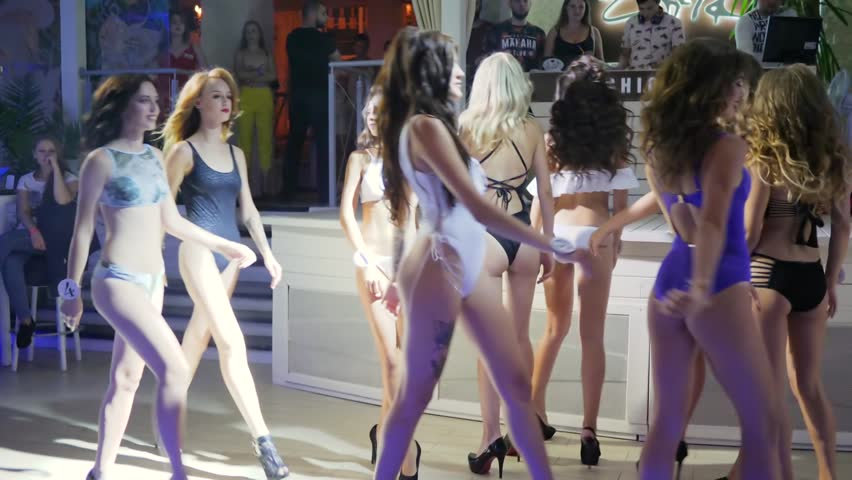 Kherson, Ukraine 12 August 2017: Miss Zefir Event beautiful girls in swimsuits are dancing at center of dance floor, group slender of girlfriends in bathing suits make show in Kherson, 12 August 2017. #33928282