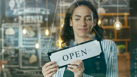 Beautiful Young Cafe Owner Turning Storefront Sign From Close to Open and Welcoming Her New Customers into Her Modern Looking Stylish Coffee Shop. Shot on RED EPIC-W 8K Helium Cinema Camera.