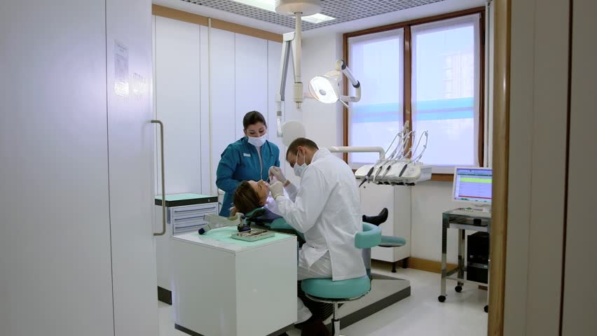 Health care in dental clinic, people working as dentist and medical assistant, checking hygiene of female client. Sequence of steadicam wide and medium shots