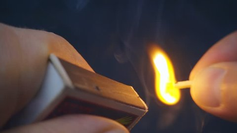 The match in the hand moves on the side of the matchbox and light the fire. S-log - High Dynamic Range. Macro. Closeup. Shallow depth of field. Slow mo, slo mo, slow motion, high speed camera, 240fps,
