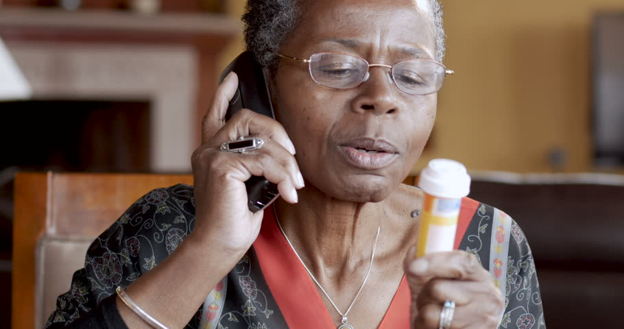 Cheerful African American senior woman finishing refilling her prescription or conversation with her doctor or health care provider.