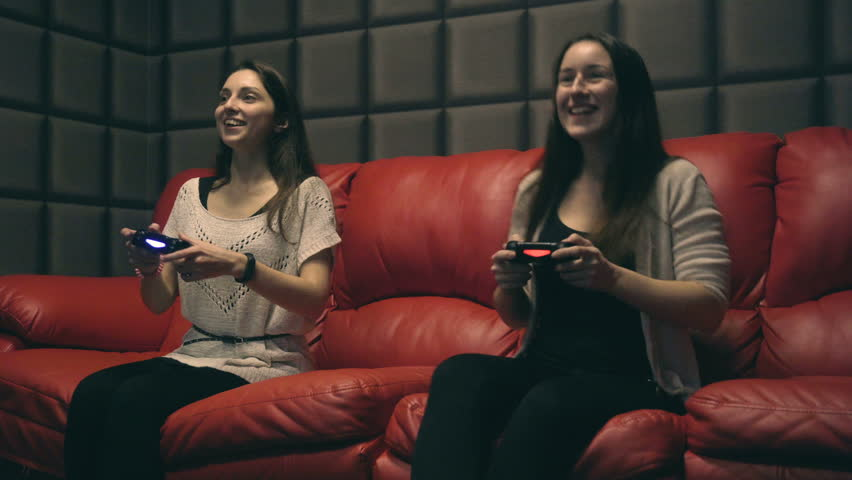 Two young girls playing video games with game controller on red sofa | Shutterstock HD Video #33974002