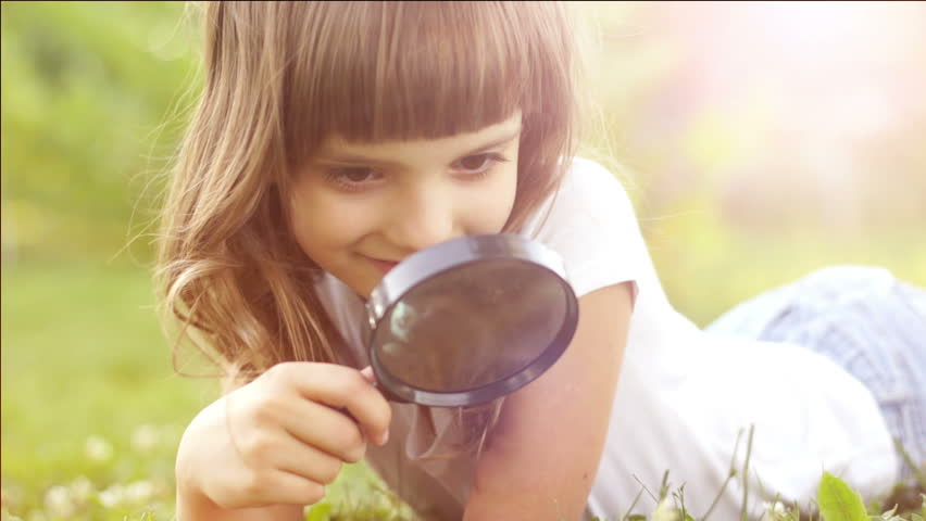 Portrait girl with magnifier lying on the grass outdoors in sun lights
