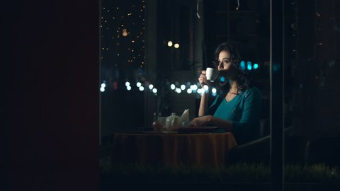 Cute womanin in a cafe.  Slow motion. A pretty woman is sitting in a cafe behind the glass and drinks tea or coffee.  The glass reflects the traffic of urban transport.