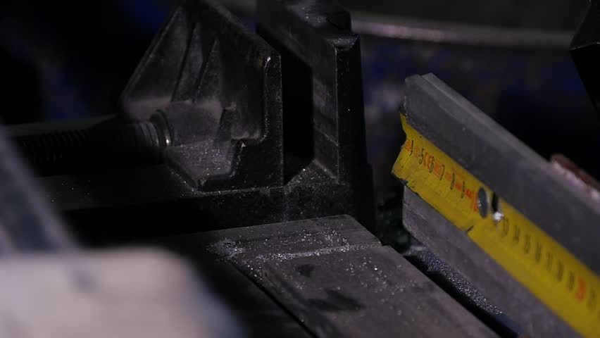 Action shot of speeding industrial bandsaw blade with coolant, showing motion blur. Frozen action shot of bandsaw blade showing teeth and coolant. band saw machine in working. Bandsaw power tool which