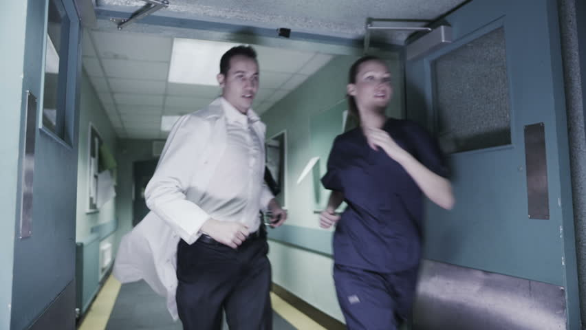 Doctor's and medical staff burst through a set of double doors and are running through a hospital corridor to reach a reported emergency. In slow motion.