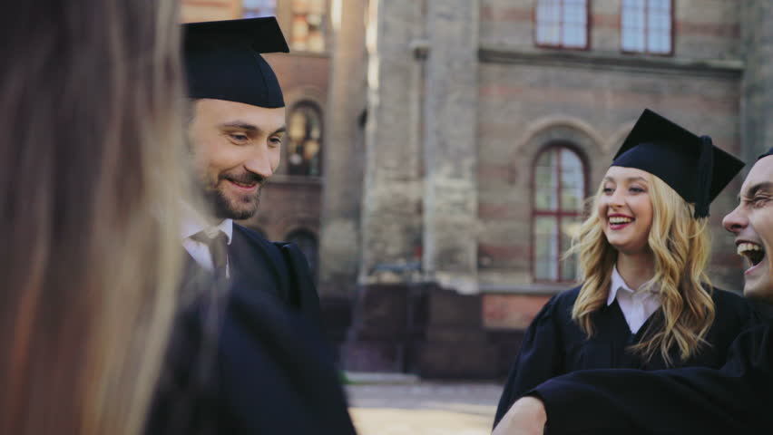 Caucasian male and female graduates holding their diplomas and talking after the graduation day at their University building. Outside
