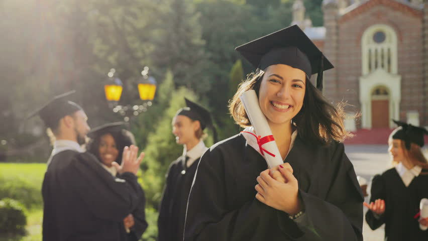 Portrait of the happy beautiful young female graduate in a traditional clothes and cap smiling to the camera and holding her diploma on a sunny day. Multi ethnical students on the background. Outside | Shutterstock HD Video #34025422