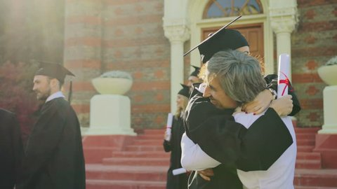 Gray-haired good looking father congratulating her daughter in special clothes with the graduation at the University entrance. Outside