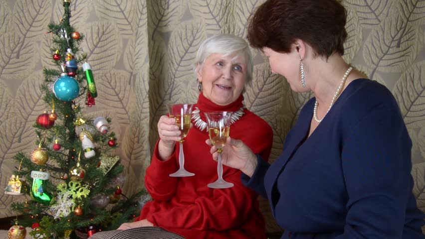 senior grandma and mature woman at new year midnight clinking glasses. old  grandmother and her daughter drink wine, smiles, laugh. happy company near  ...