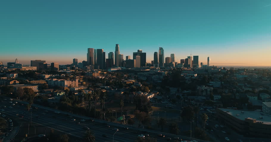 Cinematic aerial drone footage of downtown urban Los Angeles with city skyline, freeway and traffic below.
