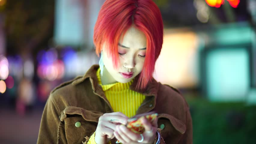 Modern teenage Chinese girl uses smart phone. Non traditional rebellious young Asian woman with colored hair uses phone on street at night. Alternative punk youth downtown in evening.