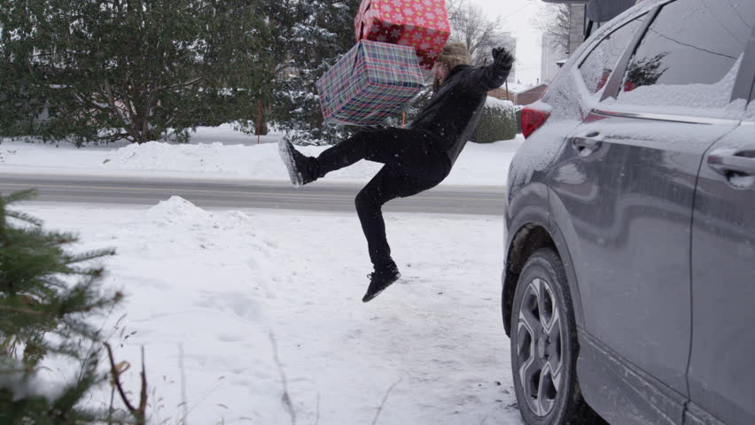 Man slips in slow motion carrying christmas gifts