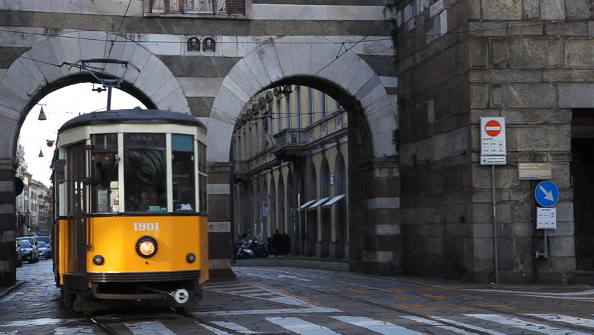 MILAN, ITALY - DECEMBER 29, 2011 Old Yellow Tramway Traffic on via Manzoni, Busy City Traffic on Italian Crowded Street, Commuters Commuting Morning Transit