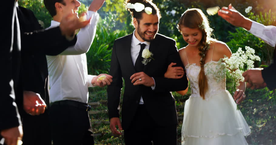 Bride and groom walking down while guests toss petals at wedding 4K 4k
