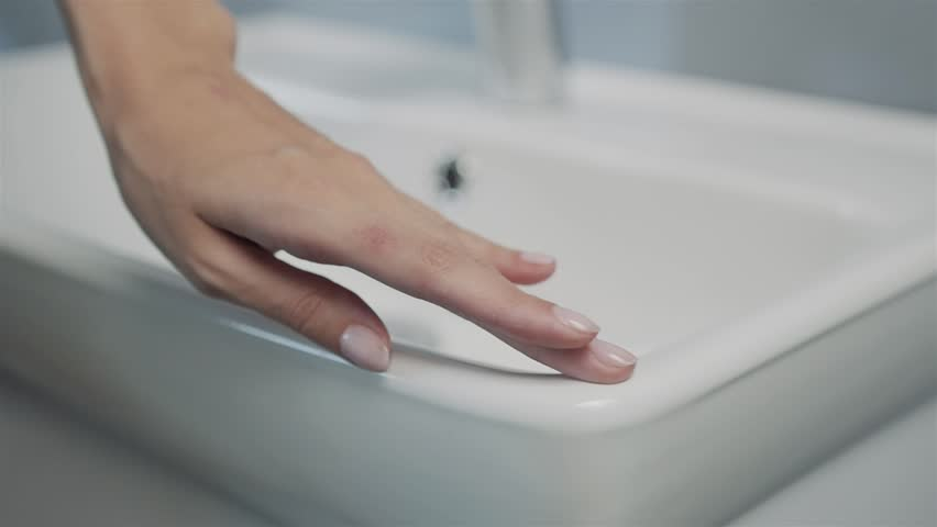 Close up of female hands cleaning bathroom sink, hand new furniture