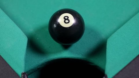 Close up of a billiard ball number 8 with black color falling into the billiard table hole