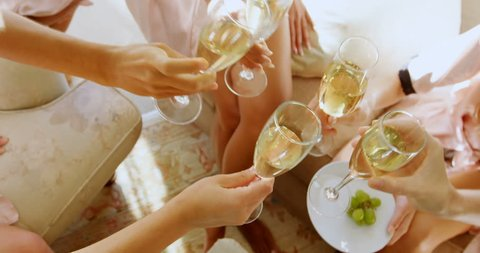 Bridesmaids in nightdress toasting a glass of champagne at home 4K