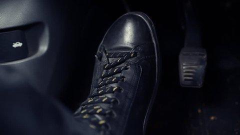Feet pushing car coupling pedal, close up